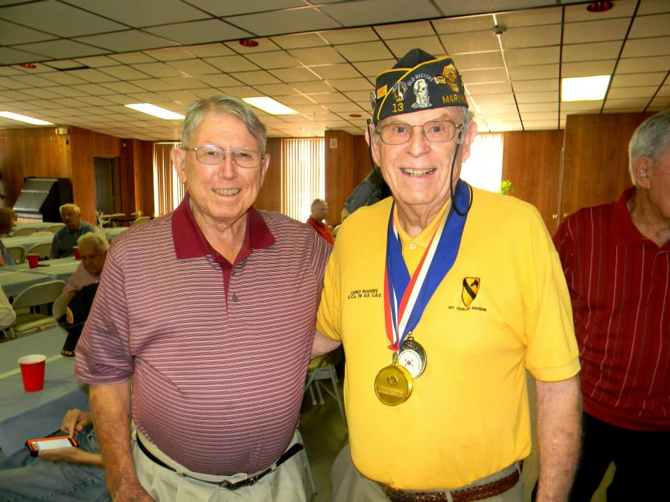 Man in red shirt standing and smiling with man in yellow shirt and Korean War veteran hat