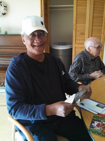 Veteran in white hat picking up cards off the table, looking into and smiling at the camera