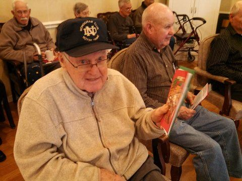 Man, in grey sweater and Notre Dame hat, sitting holding up card and smiling