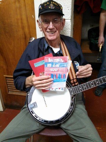 Image of sitting man with banjo on lap, holding up multiple cards and smiling