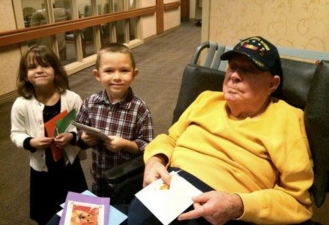 A boy and girl kneeling beside veteran in yellow shirt who is sitting, with cards in lap