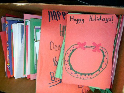 Image of piles of cards in a box, the top one says happy holidays with a drawing of a wreath