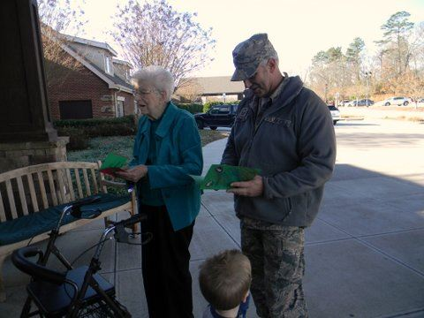 Image of older womanwith a walker and younger man receiving thank you cards