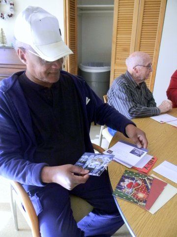 Veteran in white hat picking up cards off the table