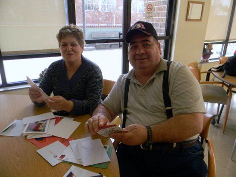 Man and woman sitting at table with a pile of cards in front of them, both are looking into the camera smiling