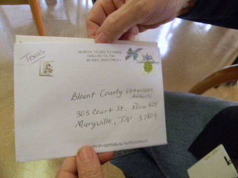 Image of hands opening a white envelope postmarked from Texas.