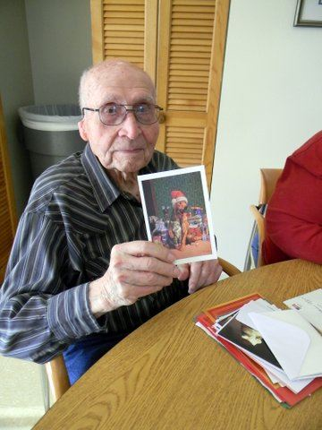 Sitting veteran with glasses hold up a holiday card