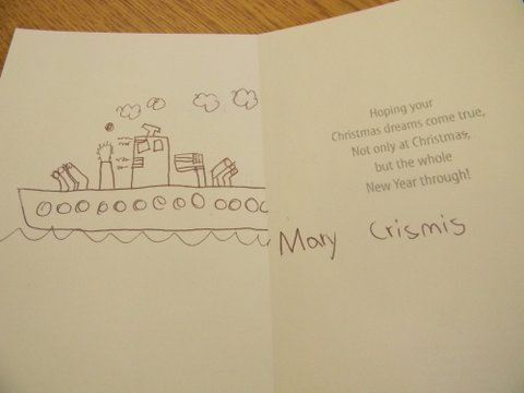 "Image of interior of card, left side has drawing of a ship, right side has children's handwriting ""Mary Crismis"""