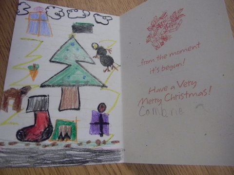 Interior of card, left side has child's drawing of Christmas tree, stocking, reindeer, clouds, and presents
