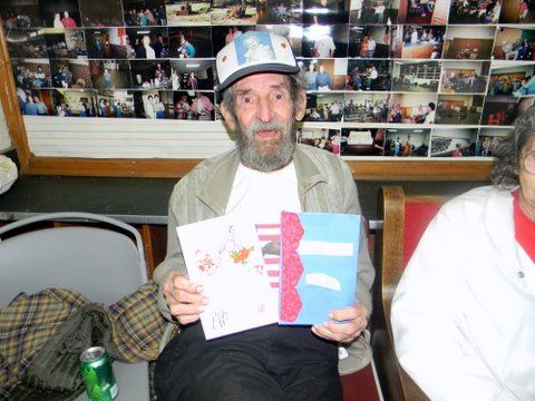 Image of sitting veteran holding two cards up for display