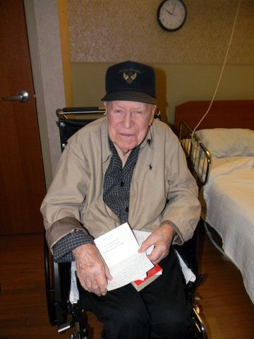 Image of veteran in khaki coat and black hat in wheelchair, with cards on his lap