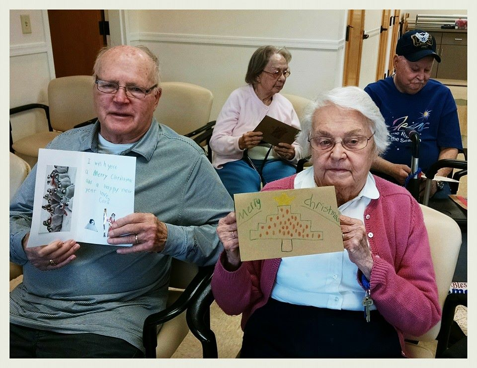 Two sitting veterans, one man and one woman, holding cards with Merry Christmas written on them in children's handwriting