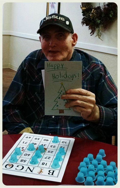 Man playing BINGO holds up Happy Holidays card