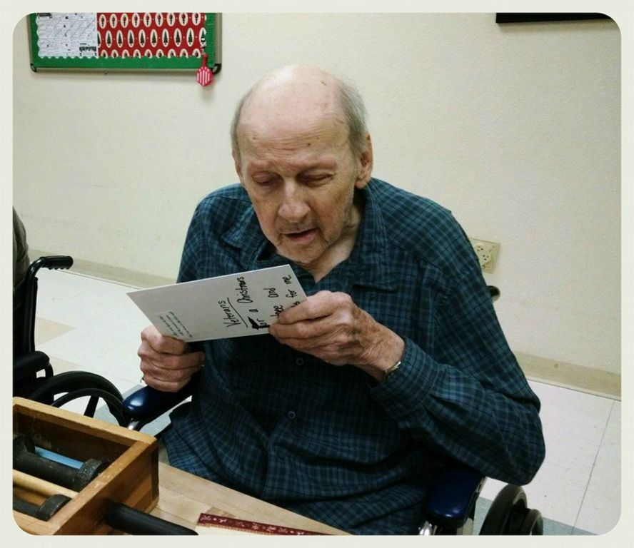 Veteran in dark blue plaid reads card with merry Christmas