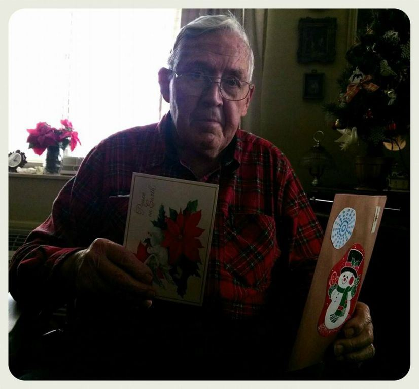 Veteran with glasses and red plaid shirt sits holding up two cards