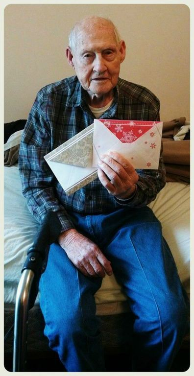 Veteran in blue plaid and jeans sits on edge of bed, holding up two envelopes