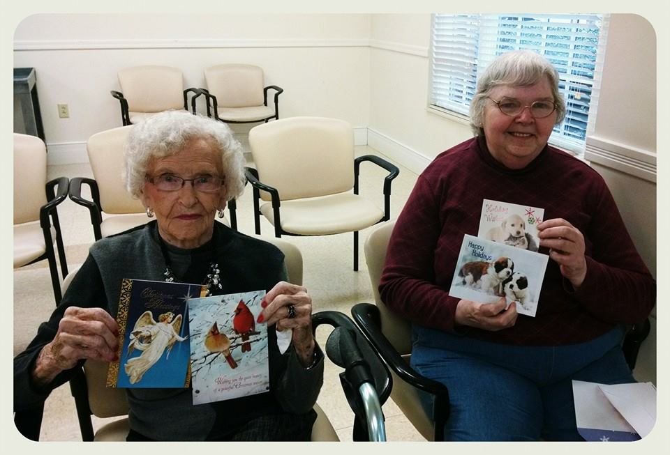 Two women veterans sit holding up cards for the camera