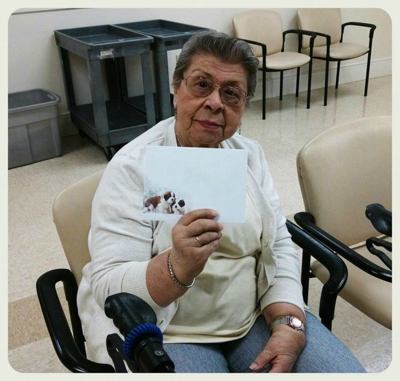Sittign woman veteran holds up card for camers