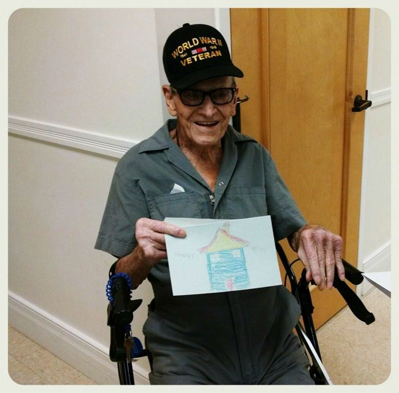 Man sitting in walker wearing glasses and World War II Veteran hat, holds up card with house drawn on it