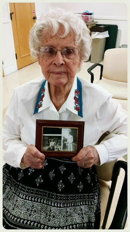 Woman in white shirt looks into camera and holds black and white photographs of soldier