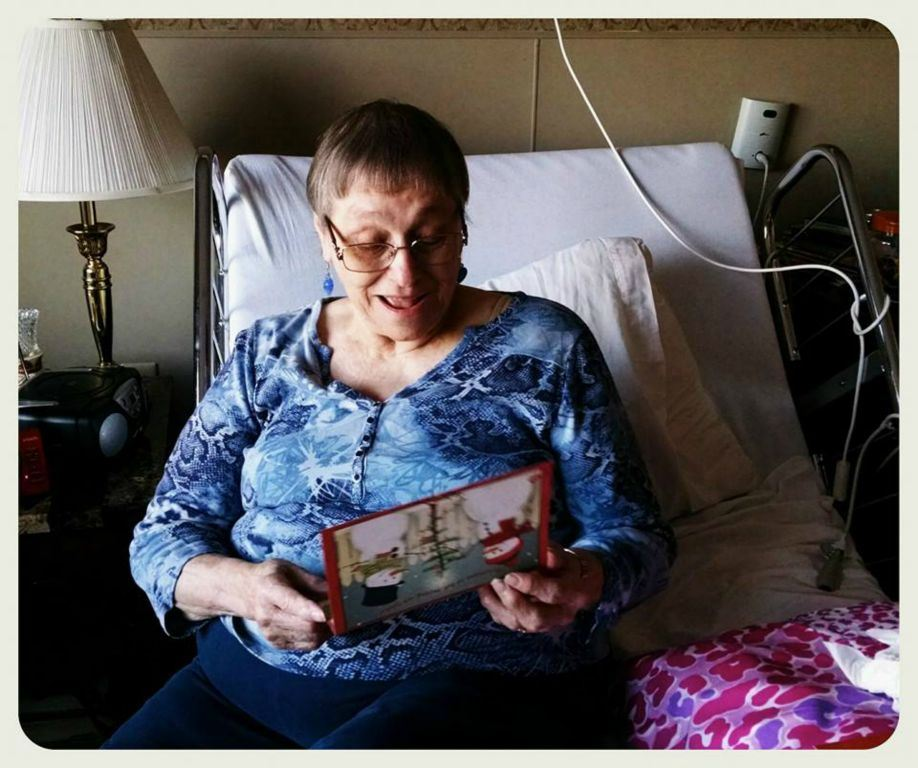 Smiling woman reads card, sitting on bed