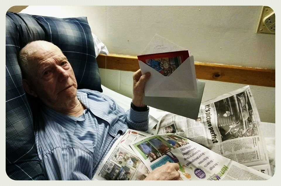 Veteran lies back with newspaper on lap to display holiday card to viewer