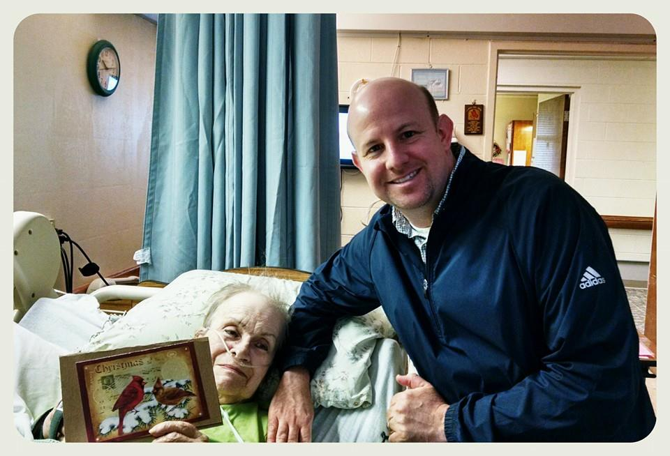 Woman veteran smiles while holding up card, with visitor standing by her bed