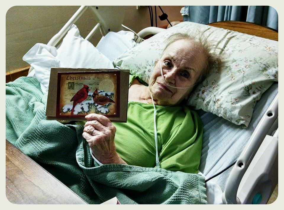 Smiling woman veteran lies back while showing off holiday card to camera