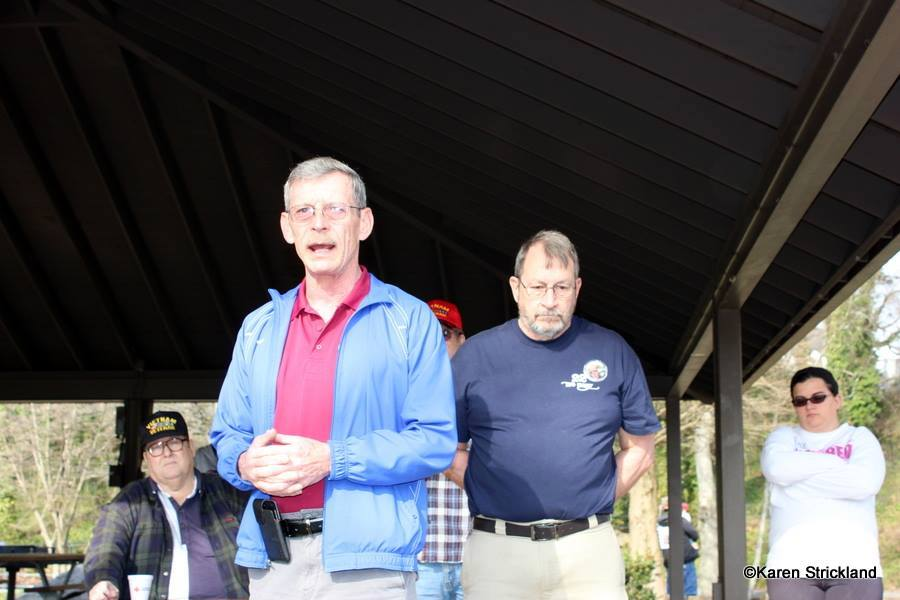 Man in blue jacket and red shirt speaks with hands folded