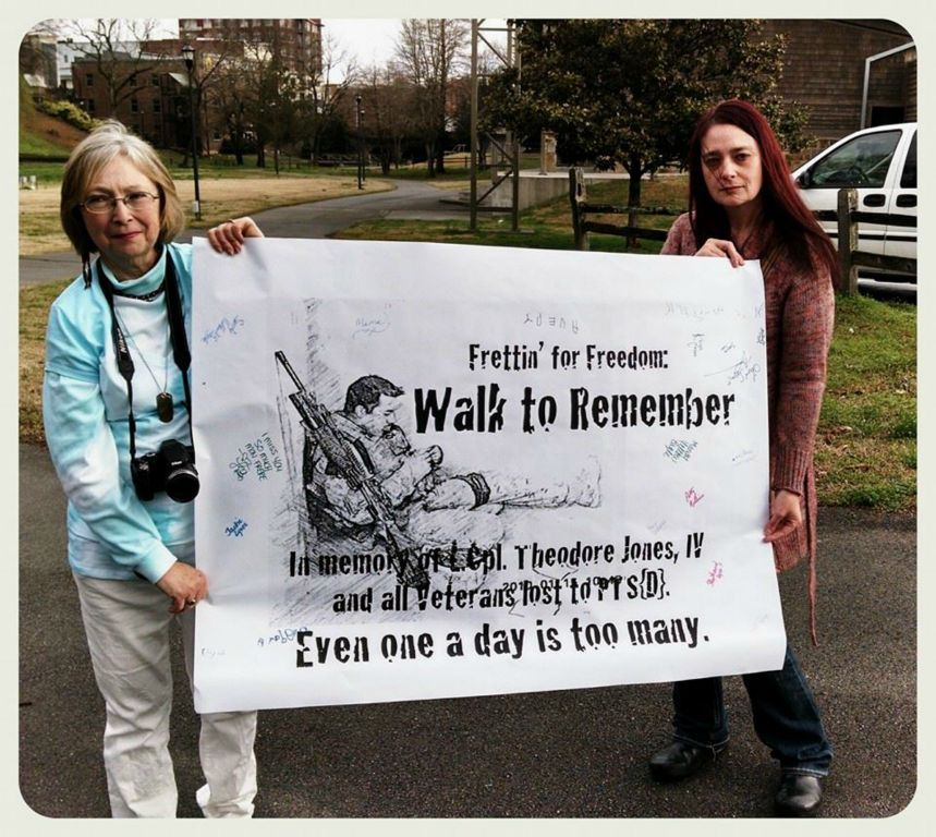 Two women walk stand,  holding poster for Theodore Jones, IV