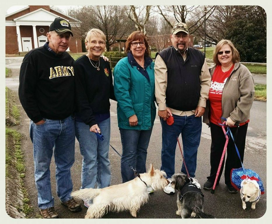 Five participants stand together smiling, three with dogs on leashes