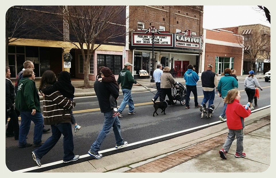 Awareness groups walks down main street, in front of theatre.