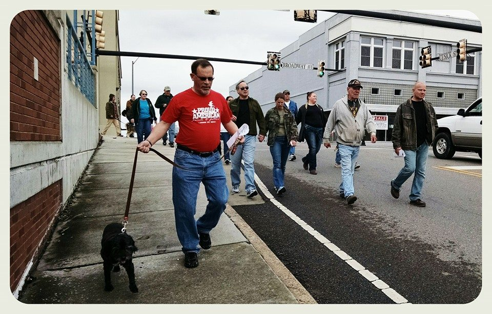 Man in red Proud american shirt walks black dog down street with Awareness walkers