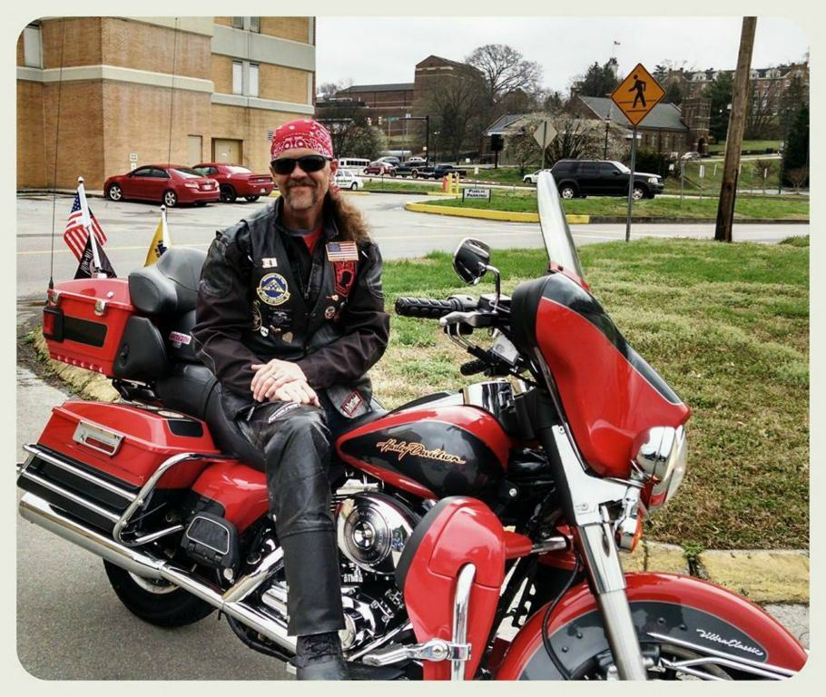 Man in black sits astride red motorcycle