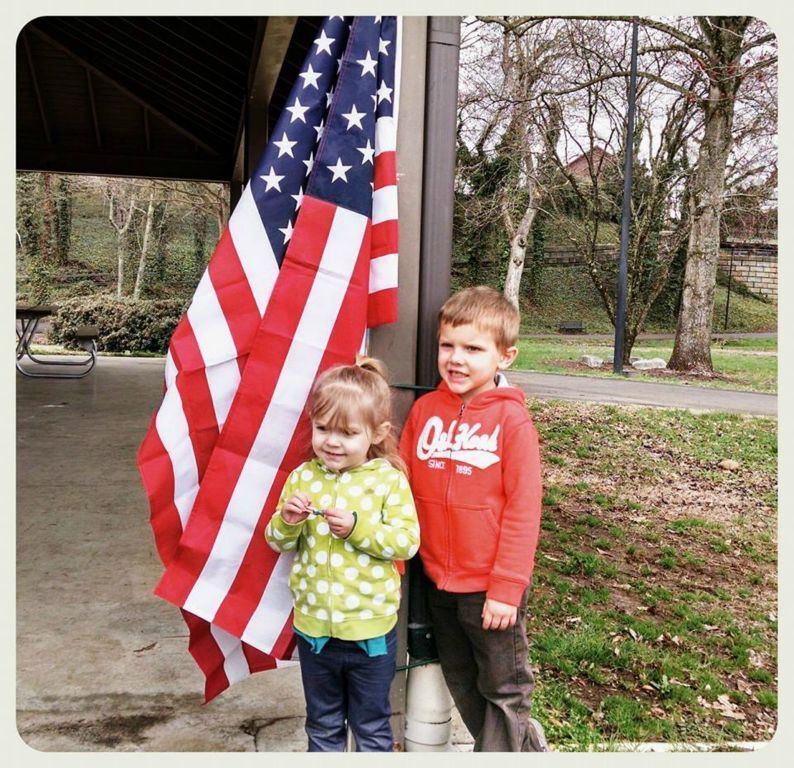 Two children stand in front of American flag