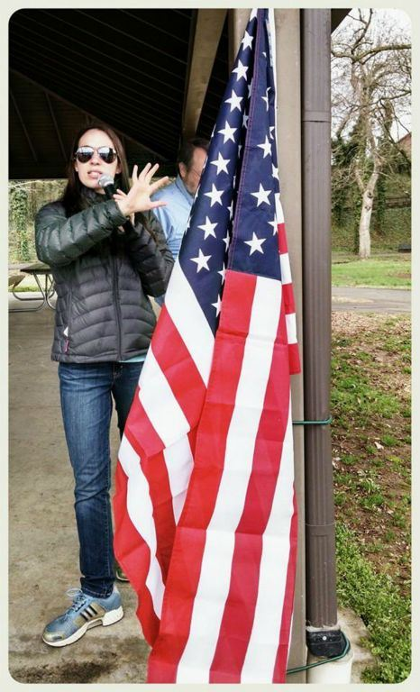 Woman with microphone stands with hand pointing to American flag