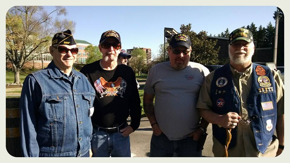 Four men with war hats stand together smiling into camera