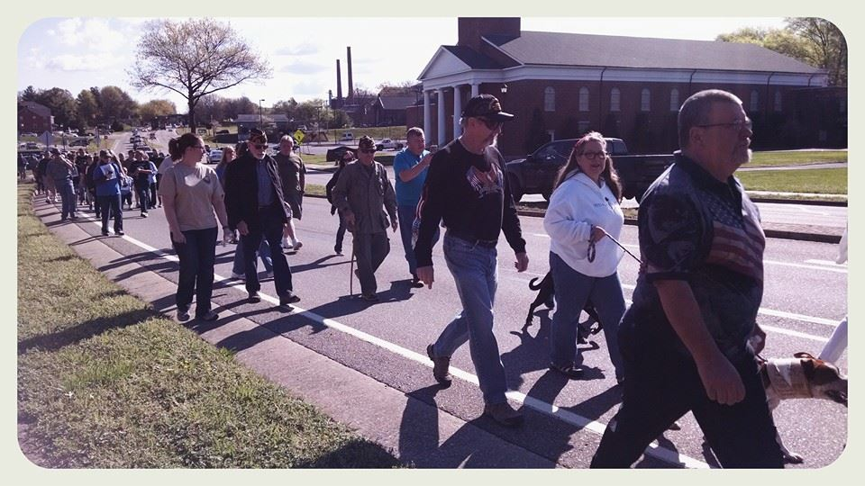 Image of smaller groups making the larger walking group, some with dogs, in front of columned church on street