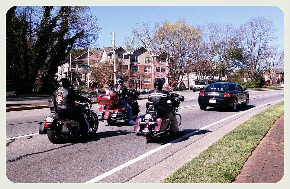 Three motorcycles follow black police cruiser