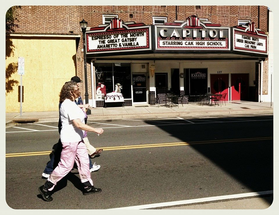 Two participants, view from side, walk in front of town theater