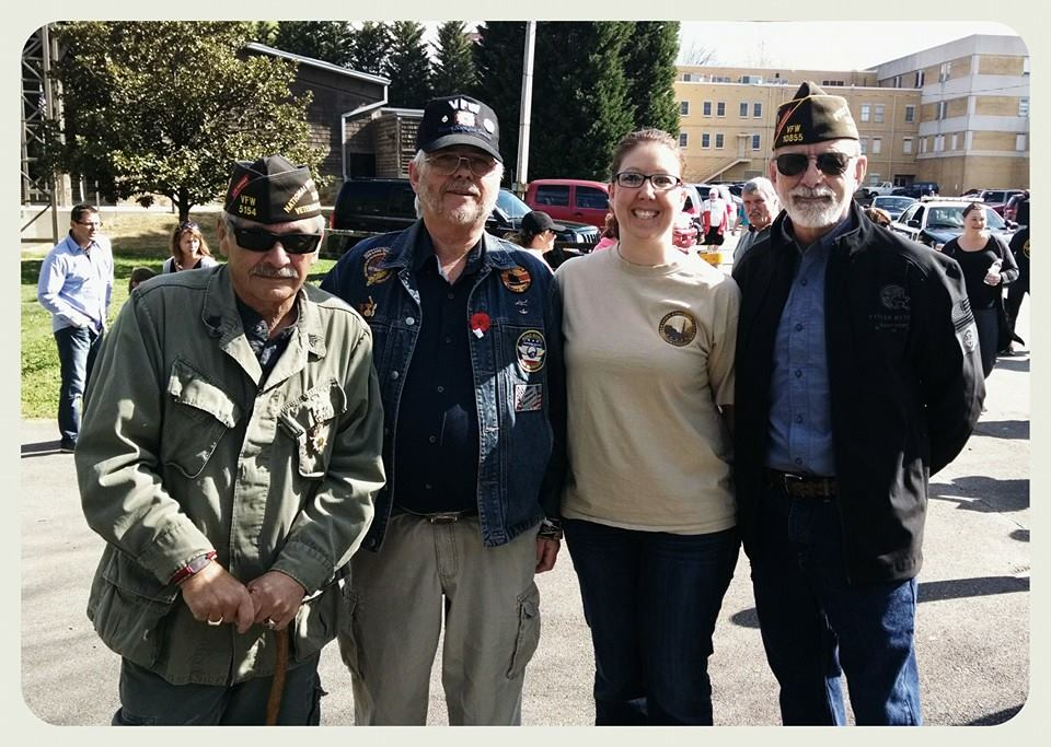 Three men with veteran's hats stand with woman looking into and smiling at camera