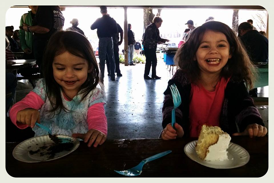 Two young girls sit beside each other enjoying cake at a picnic table
