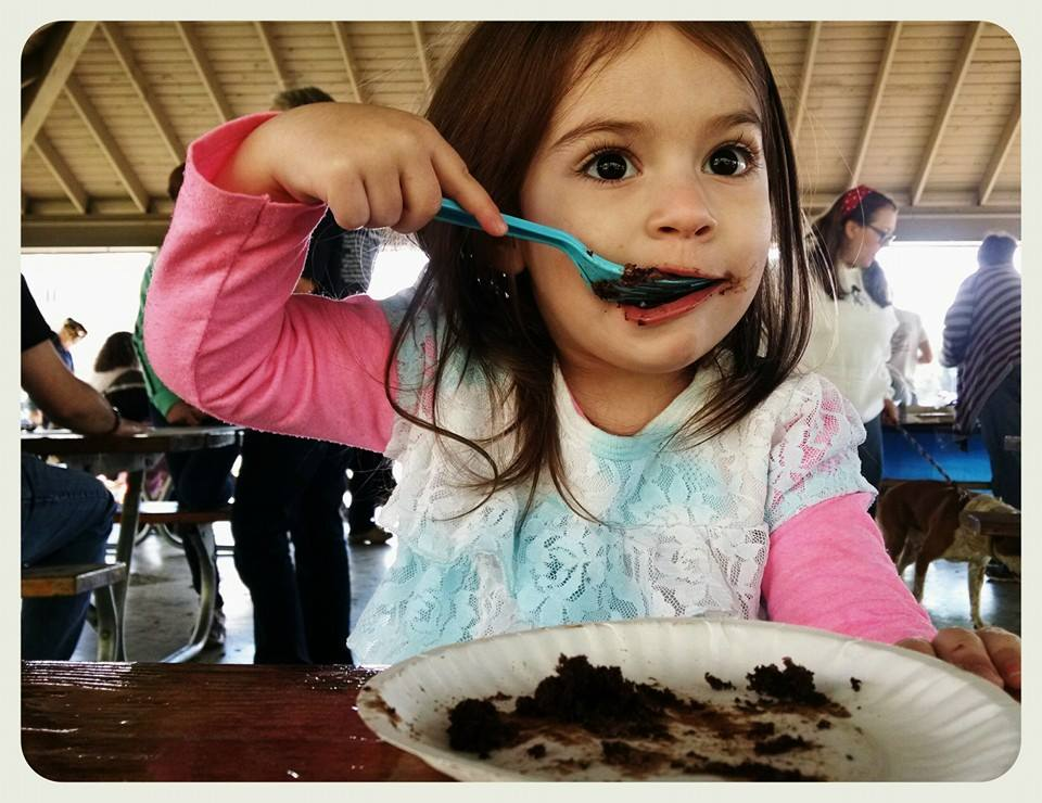 Young toddler girl, up close image of her enjoying some chocolate cake