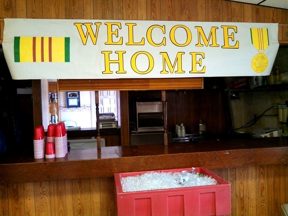 Welcome home sign mounted above a bar with red cups and red cooler