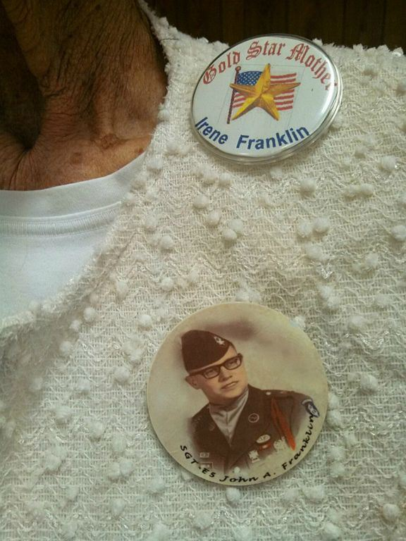 Up close image of pins, one saying Gold Star Mother Iren Franklin, the other with a picture and the text Sgt. John A Franklin