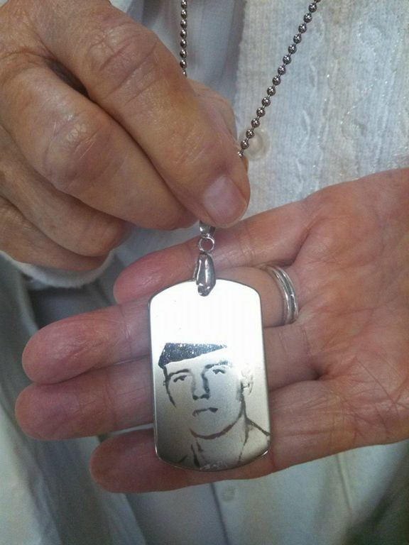 Hands hold and show portrait of soldier etched into dog tags