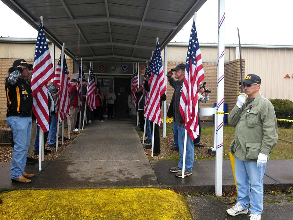 Veterans line entrance with American flags, saluting