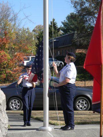 Three cadets stand at flag pole unfolding and hooking up American flag