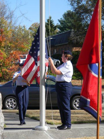Three cadets stand at flag pole raising American flag