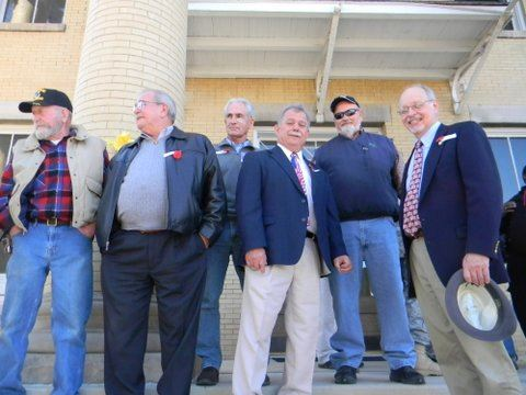 Sixe men stand on Court house steps, some smile at camera